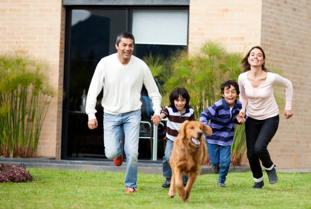 Happy family running after a dog outdoors.jpeg