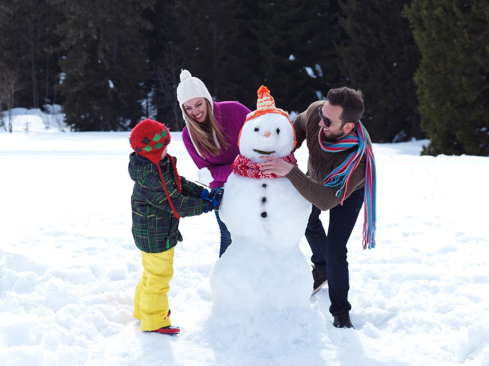 happy young  family playing in fresh snow and making snowman at beautiful sunny winter day outdoor in nature with forest in background.jpeg